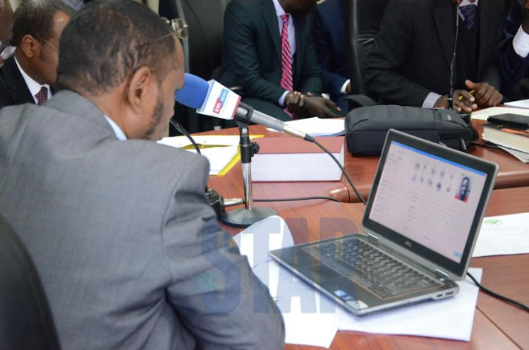 IEBC commissioner Abdi Guliye verifies the BVR machine with Mariga's details at the commission's offices on September 13, 2019.
