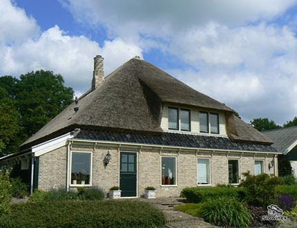 Elegancki dom z szarej cegly i kryty strzechą