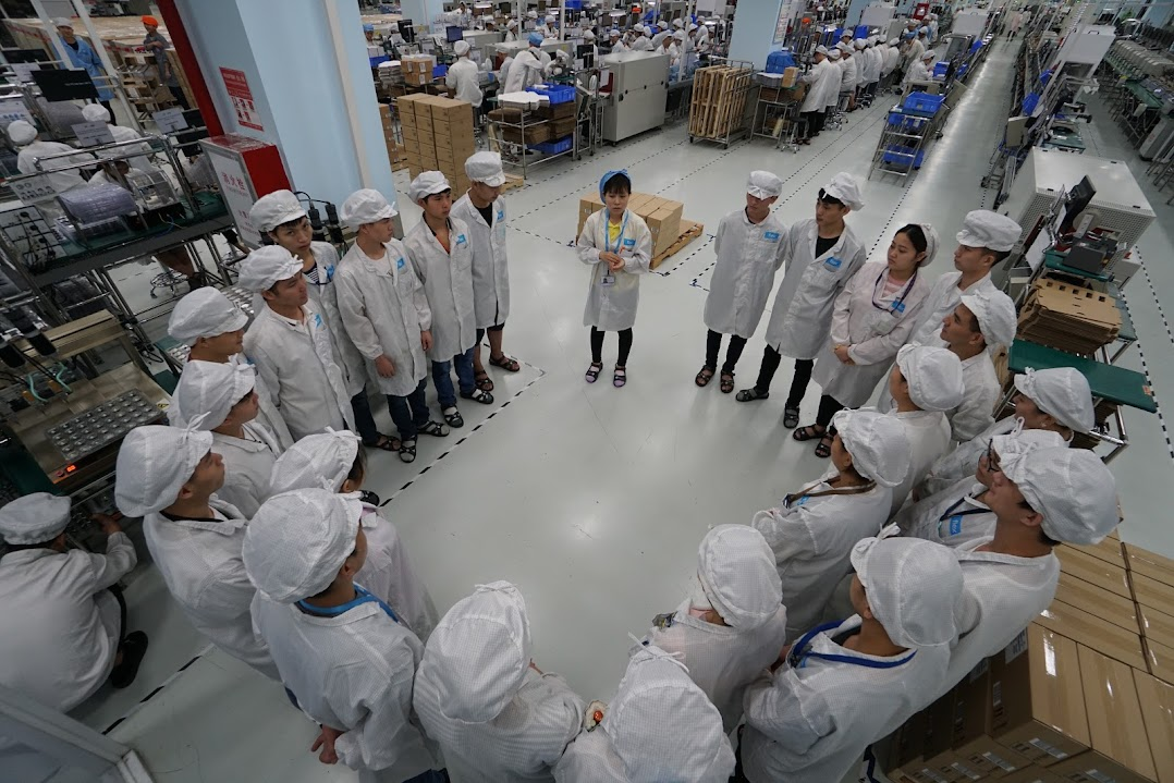A group of workers meeting on a factory floor.