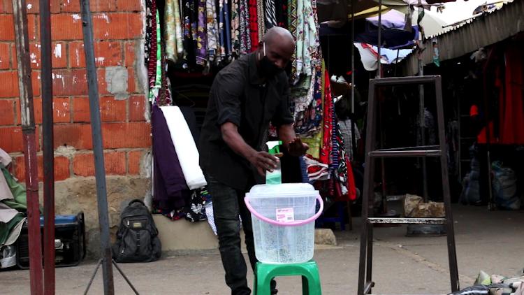 Trader washing hands at Wuse Market, Abuja.