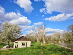 Photo: Stone hut and bridge by a pond and blossoming pear tree under blue skies at Eastwood Park in Dayton, Ohio.