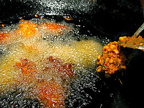 Photo: dropping spicy corn mixture into hot oil