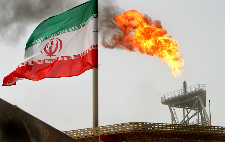 Gas flares at the Soroush oil fields behind an Iranian flag in the Persian Gulf, Iran. Picture: REUTERS/Raheb Homavandi
