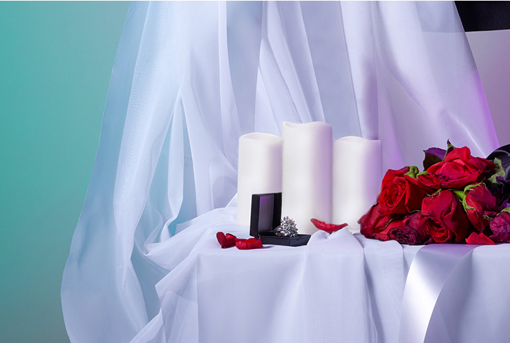 Spooky close up of zombie bride dress, LED candles and dying roses on a table