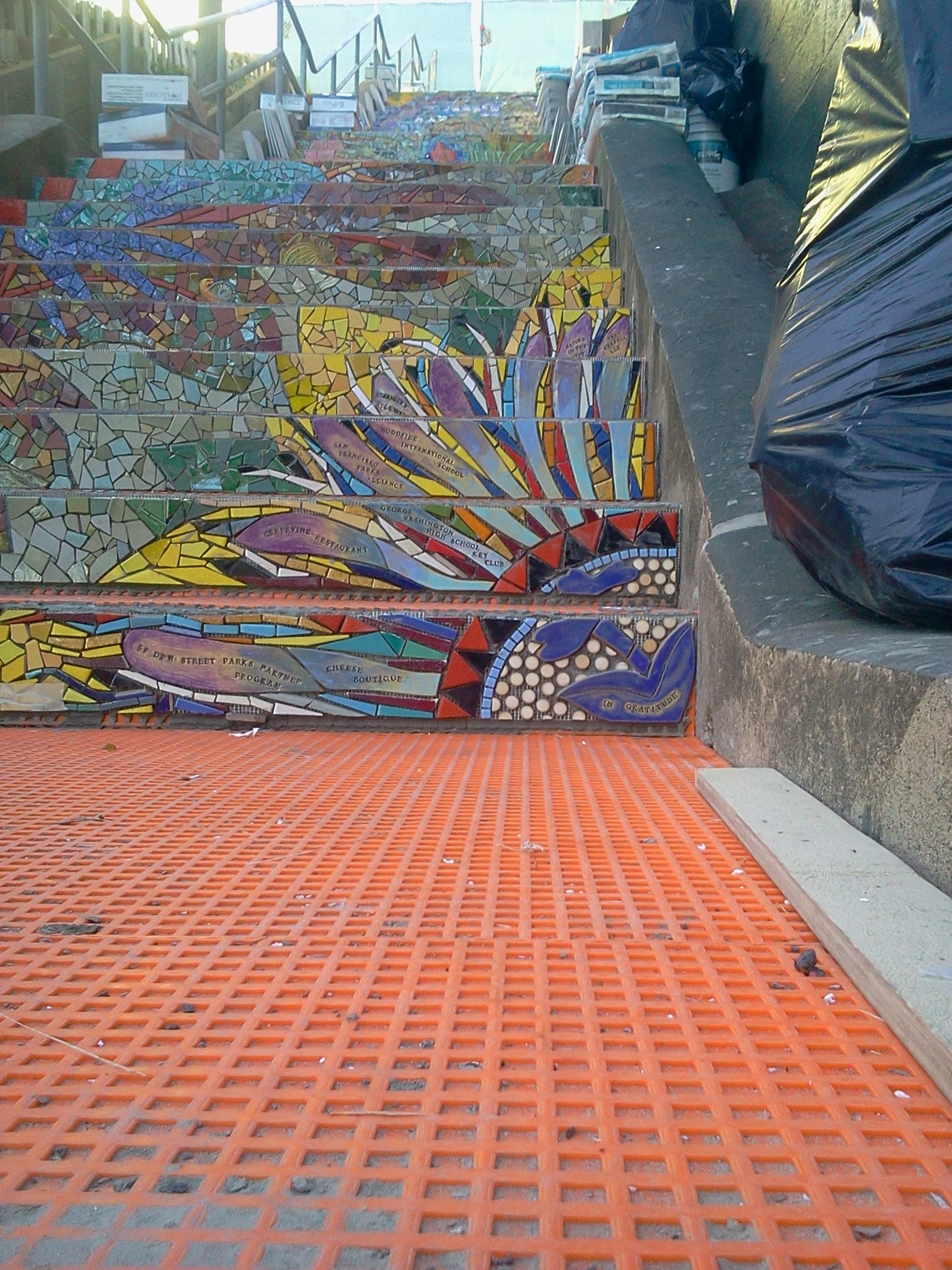 "Photo: Detail of top half of passion flower (the ""Gratitude"" element, thanking organizations and businesses that provided substantial support and in-kind gifts) on the fifth flight of steps (from top) of the Hidden Garden Steps (16th Avenue, between Kirkham and Lawton streets in San Francisco's Inner Sunset District) installed on October 30-31, 2013. KZ Tile workers finished installing more than 80 pieces of the 148-step ceramic-tile mosaic designed and created by project artists Aileen Barr and Colette Crutcher. For more information about this volunteer-driven community-based project supported by the San Francisco Parks Alliance, the San Francisco Department of Public Works Street Parks Program, and hundreds of individual donors, please visit our website at http://hiddengardensteps.org."