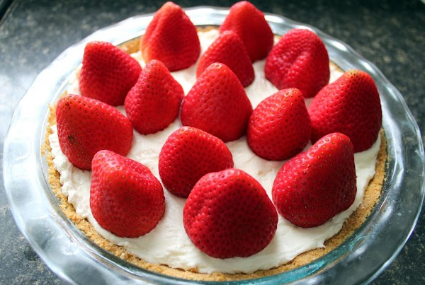 Arranging strawberries on top of the pie.