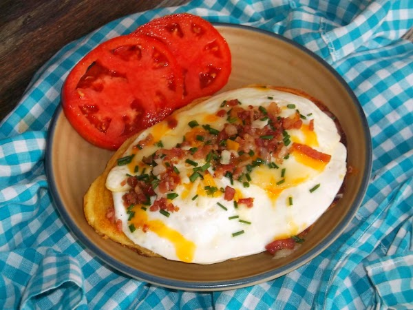 Slide eggs from skillet onto corn cake; sprinkle with chives and extra cheese and...