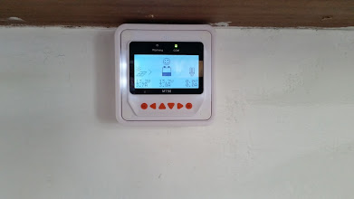 Photo: [Device replaced with a Victron unit now] View of the MT50 Remote Meter mounted under the cupboard in the kitchen with its wire running through the wall to the solar charge controller and batteries behind the wall