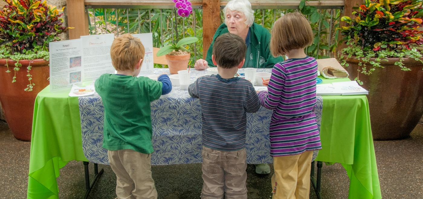 Three children are lined up at a table in Phipp's Conservatory, completing a hands-on activity with the guidance of a Phipp's employee