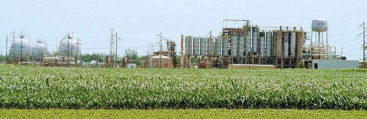 Landschaft: Felder und Chemiefabrik.