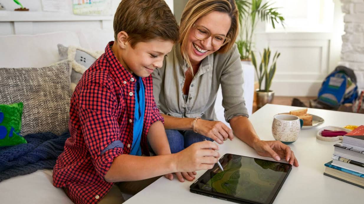 A mom working with a son using a stylus on a tablet/2-in-1 at home.