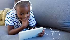 A young boy smiles as he listens to an audiobook