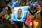 Protesters hold an enlarged picture of  teen Matlhomola Mosweu when he was  young. Two men,  Pieter Doorewaard and Phillip Schutte, are accused of his murder.