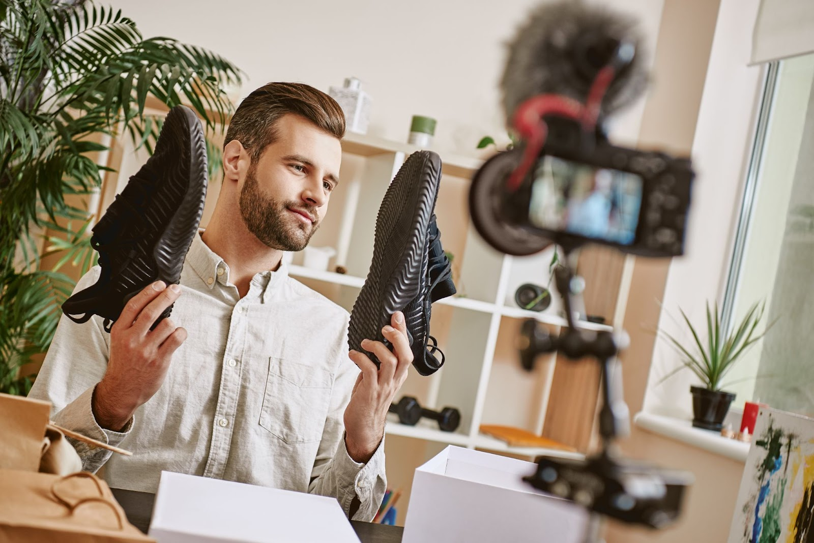 young man holds up a pair of shoes for a camera; livestreaming eCommerce concept