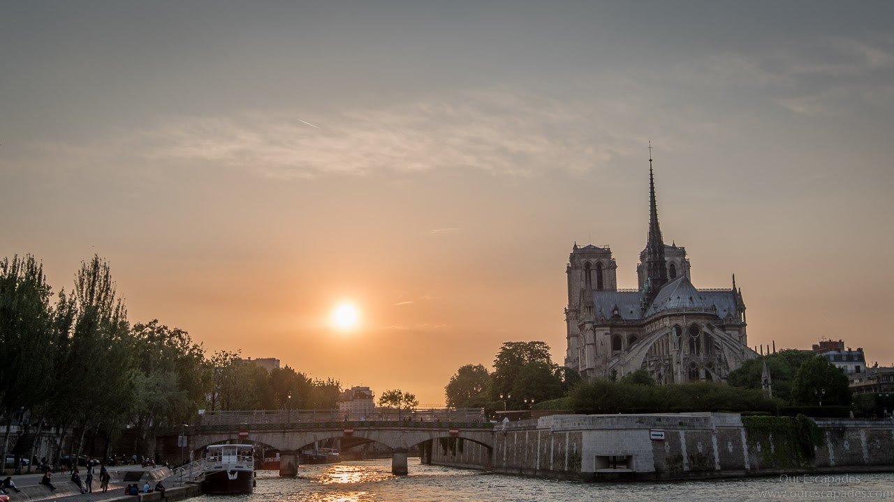 The sun sets behind Notre Dame Cathedral