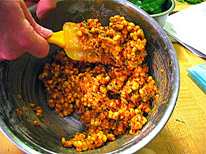 Photo: mixing corn with chilli paste and kaffir lime leaves