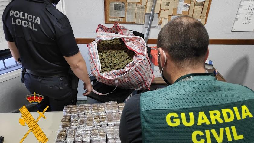 Un agente de la Guardia Civil y la Policía Local con parte del material incautado.