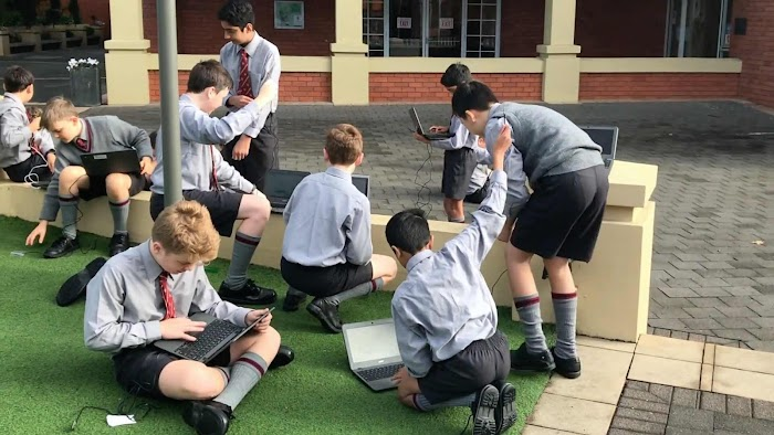Male students in school uniforms working on laptops in outdoor patio