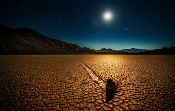 Photo: Mysterious Moving Rocks - Your Theory?  Why do you think these rocks-full-of-wonder move across the desert on their own?  I took this photo last night in a remote part of Death Valley. I'd love to read your thoughts and theories as to why and how these rocks move across the playa! Now, let's all be sporting about this and NOT use the Google to figure it out… use your mind.  The day in Death Valley was about 115 F (46 C). It wasn't a dry heat either… there has been a lot of humidity here and there is flash lightning in the day and night. This location here took a lot of time, effort, and 4x4 to find. I took five gallons of water, a map, and some warnings from the place that rented the jeep that this area was inaccessible because of recent road wash-outs from rivers. Well, they were right! So getting the 4x4 over and through the washed out rivers took many more hours than expected. I only suffered one minor injury when my head slammed into the rollbar during a clumsy maneuver.  But finally, after I finally found this place I've always wanted to visit, it was late afternoon with plenty of time to hike around before night fell.  Here are a few things I noticed which will either be a help or a hindrance in your quest to figure it out:  - When I rapped upon the rock with my knuckle, I felt a faint metallic ting. - Many rocks were jet-black and heavy with time. - The mud was dry as an old bone, and as I walked across it, I left no footprints behind. - I walked around without my shoes for a bit, and my feet barely picked up any sand or dirt. There was a fine white-alkaline powder on my soles, however. - I never saw the rock move, but I did try something. In the still of the night, if you put your ear to the ground near the rock, you can hear a distant echo - a trembling sound from deep underground, like heavy chains dragged through the maw of hell.  So what do YOU think causes the rocks to move? Give me your best AND most ludicrous theories!  In the meantime, I'm lea
