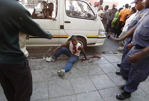 An injured man beaten in a mob justice incident- after The Red Ants evicted illegal tenants from a building on the corner of Jeppe and Nugget Street in Johannesburg. Pic: Alon Skuy. 16/10/2007. © The Times.