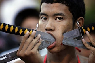 Photo: A devotee of the Chinese Shrine Ban Tha Rue, with his cheek pierced with swords, looks on during ceremonies Friday, Oct. 3, 2008, at the Vegetarian Festival in Phuket, Thailand.  The festival celebrates vegetarianism and calls on devotees through self mortification to purify themselves as they take on the sins of the community.  Each of the main shrines in Phuket will hold processions. (AP Photo/David Longstreath)