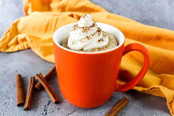 Cinnamon Swirl Snickerdoodle Mug Cake With Cream Cheese Frosting On Top.