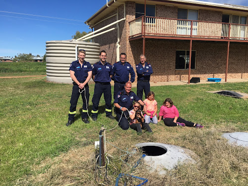 Back from the depths of the septic tank, foreground, Oscar is restored to his family after his salvation by Narrabri Fire and Rescue. From left, Luke Morgan, Dave Anderson, Jason Anderson and Lachlan Blissitt, front Shane Bradford with Jorja, Rique-Lee and Isabella Hackett and Oscar.