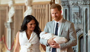 Prince Harry, Duke of Sussex, and Meghan, Duchess of Sussex, pose with their newborn son, Archie, in St George's Hall at Windsor Castle on May 8.