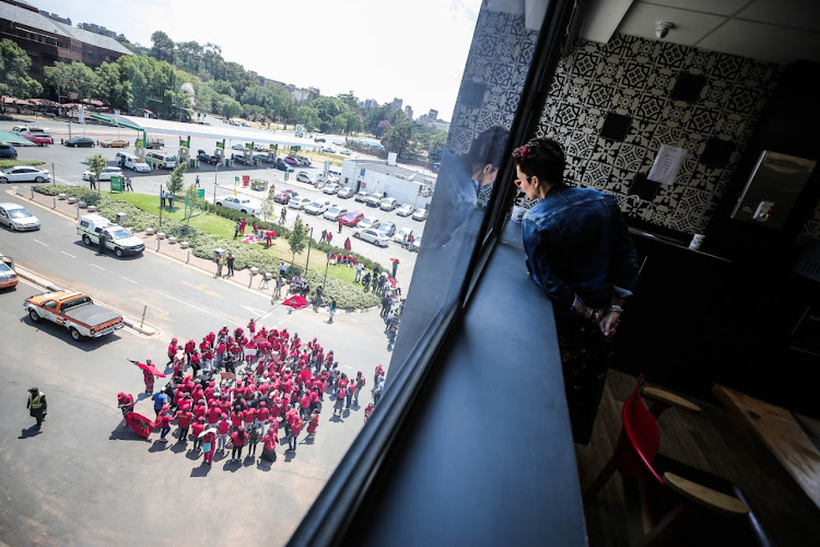 A staff member at Hill on Empire watches on as members of the EFF protest alongside members of the BLF outside the commission of enquiry into State Capture in Parktown, Johannesburg.