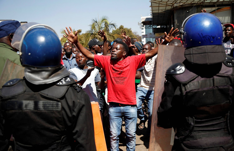 A supporter of the Movement for Democratic Change (MDC) opposition party of Nelson Chamisa gestures to the riot police as they march on the streets of Harare, Zimbabwe