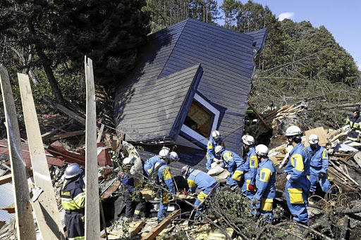 Frantic search: Rescue workers sift through debris looking for survivors from a house damaged by a landslide caused by an earthquake in Atsuma town, Hokkaido, in Japan in this photo taken by Kyodo on Thursday.