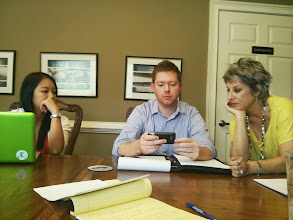 Photo: Stephenie Lai, a VISTA with HandsOn Tech Atlanta, looks on as skills-based volunteer Jon Whitaker demonstrates the new mobile version of the Cherokee Family Violence Center's website to Meg Rogers, Executive Director.