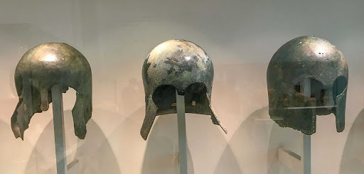 Greek-bronze-helmets_.jpg - Greek bronze helmets from 600-700 B.C. After successful battle, helmets were sometimes bent and offered in a ceremony as an expression of gratitude to the gods.