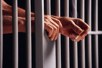 Photo: Prisoner Holding Cigarette Between Bars