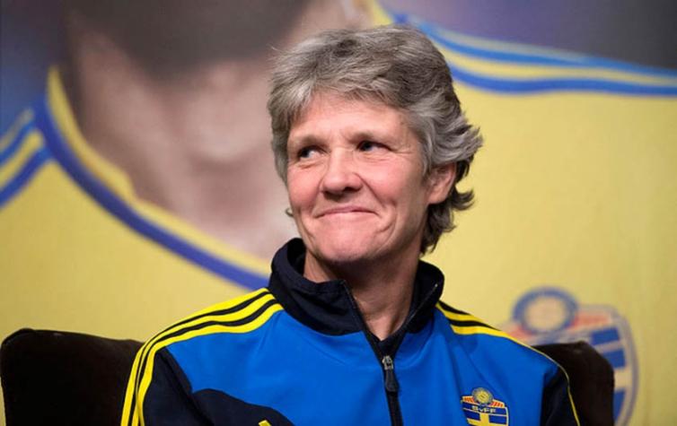#DescriçãoDaImagem: mulher branca de cabelos curtos e grisalhos no centro da imagem, sorri sem mostrar os dentes e usa casaco azul e amarelo. Foto: Maja Suslin.
