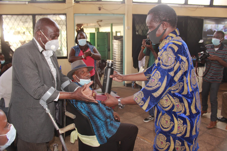 Lawyer PLO Lumumba, a trustee of Wasee wa Zamo, hands Elijah Gitonga his induction award at the Jericho Social Hall