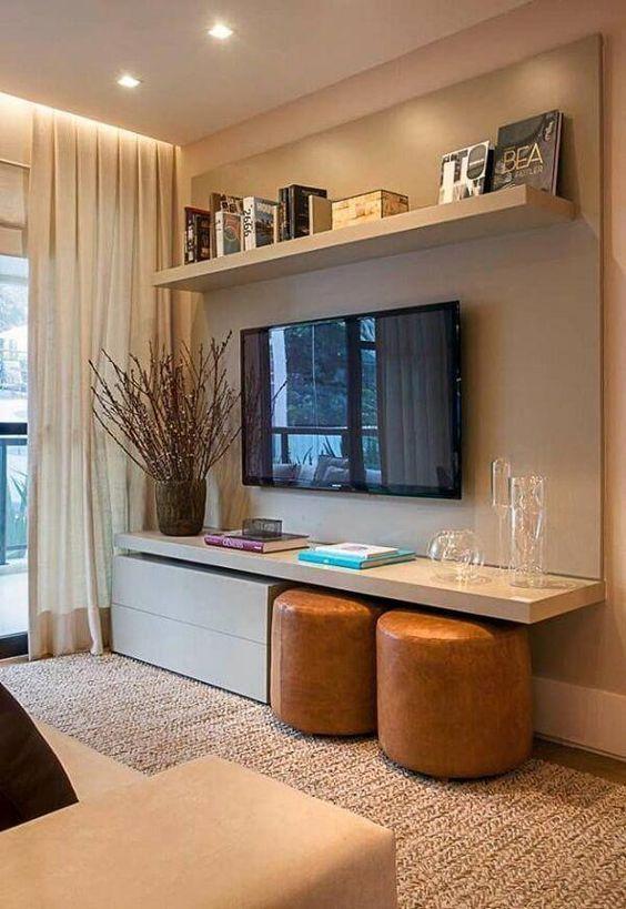 Sala com hack com TV e prateleiras com livros e vasos decorativos.