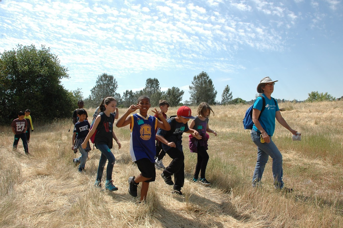 This image shows a woman leading a group of students across a grassy hill.