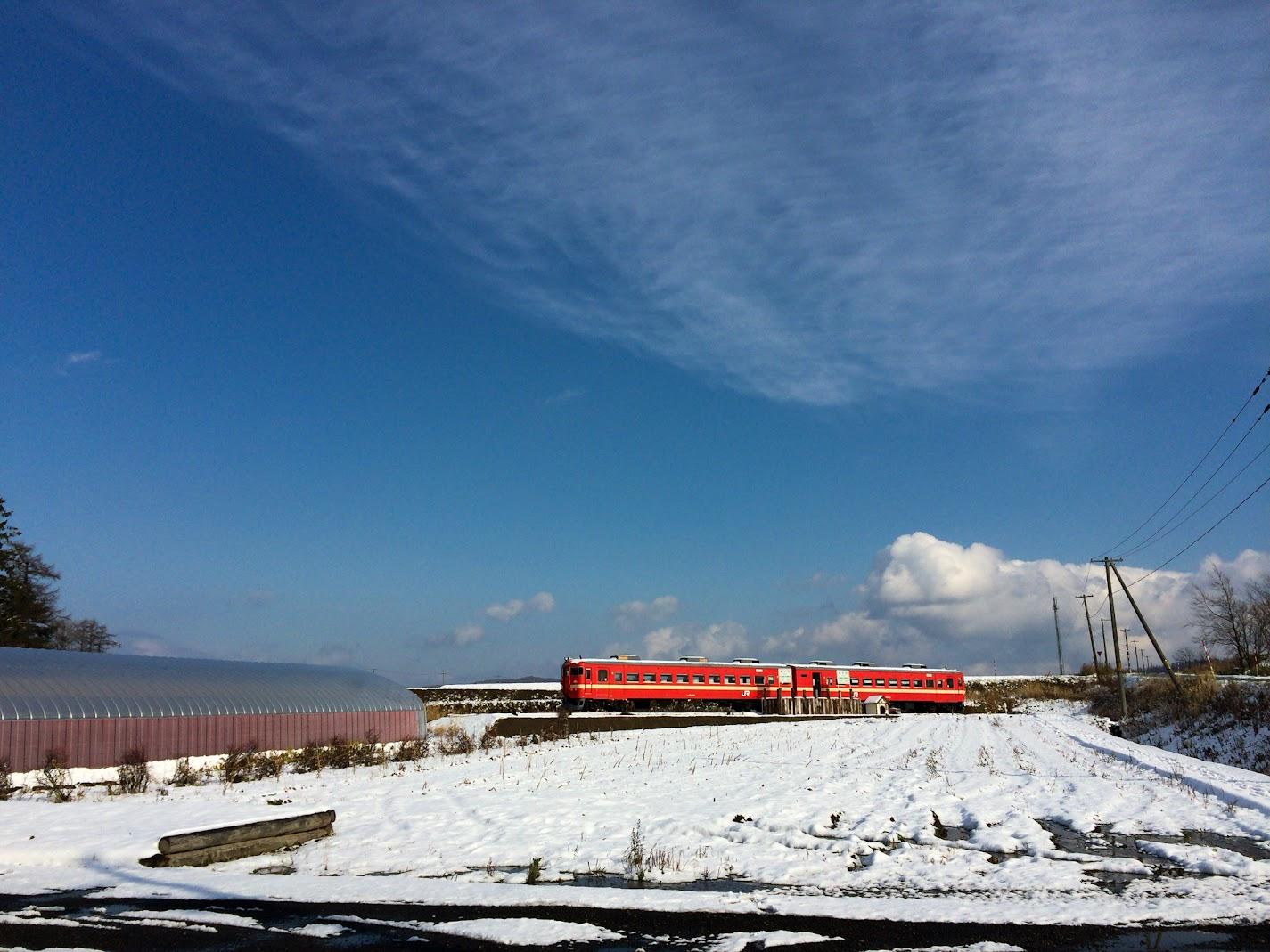 青い空と白い雪と赤い電車の風景