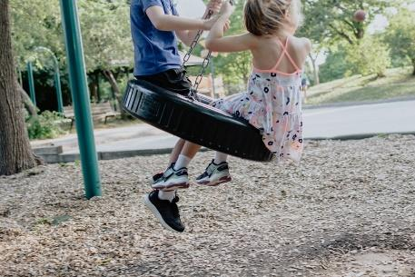 girl in pink and white floral dress riding on swing during daytime