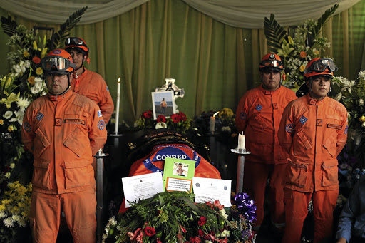 FALLEN HERO: Rescuers stand by the coffin of colleague Juan Fernando Galindo during his wake in Alotenango on June 5 2018. Galindo died trying to rescue people during the Fuego eruption. Picture: REUTERS