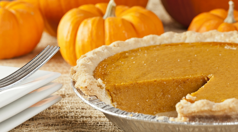 a pumpkn pie with a slice cut out of it with several small pumpkins alongside