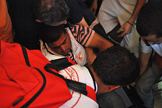 Photo: A medic passed out from tear gas inhalation is assisted by others into a nearby ambulance truck.