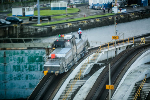 "panama-canal-mule-in-action.jpg - Electric locomotives, called ""mules,"" guide a ship through a Panama Canal lock."