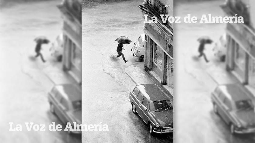 Un peatón intentando saltar por encima de un charco en la esquina entre la Plaza de Manuel Pérez y la Plaza del Carmen, frente al kiosco de Amalia.