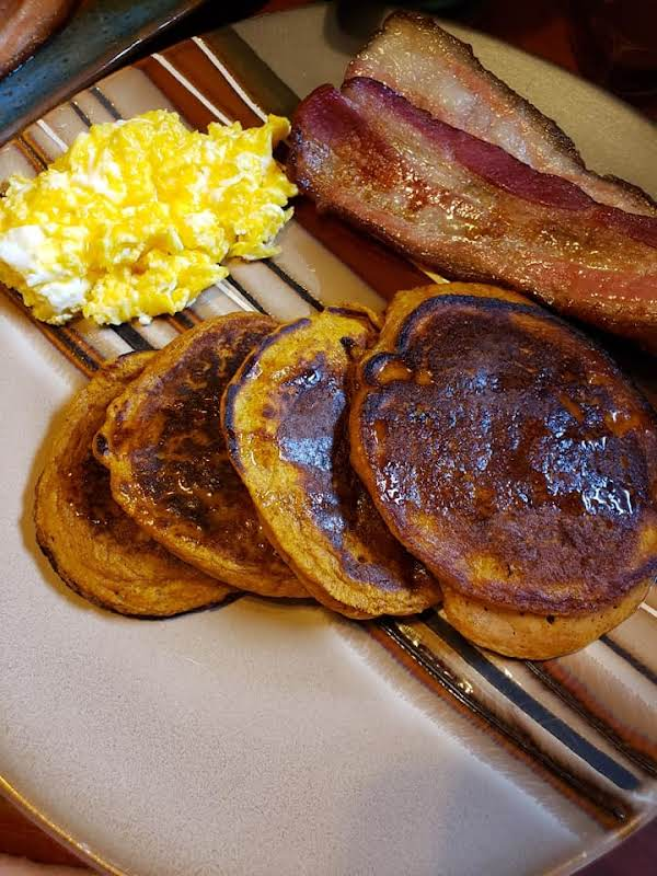 Pumpkin Pancakes Covered In Pure Maple Syrup With Thick Sliced Bacon And Cheesy Eggs