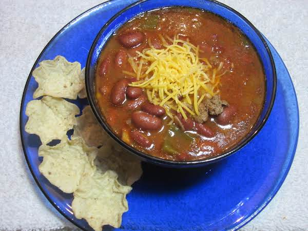 Bowl Of Chili With Shredded Cheddar And Corn Chips On The Side.