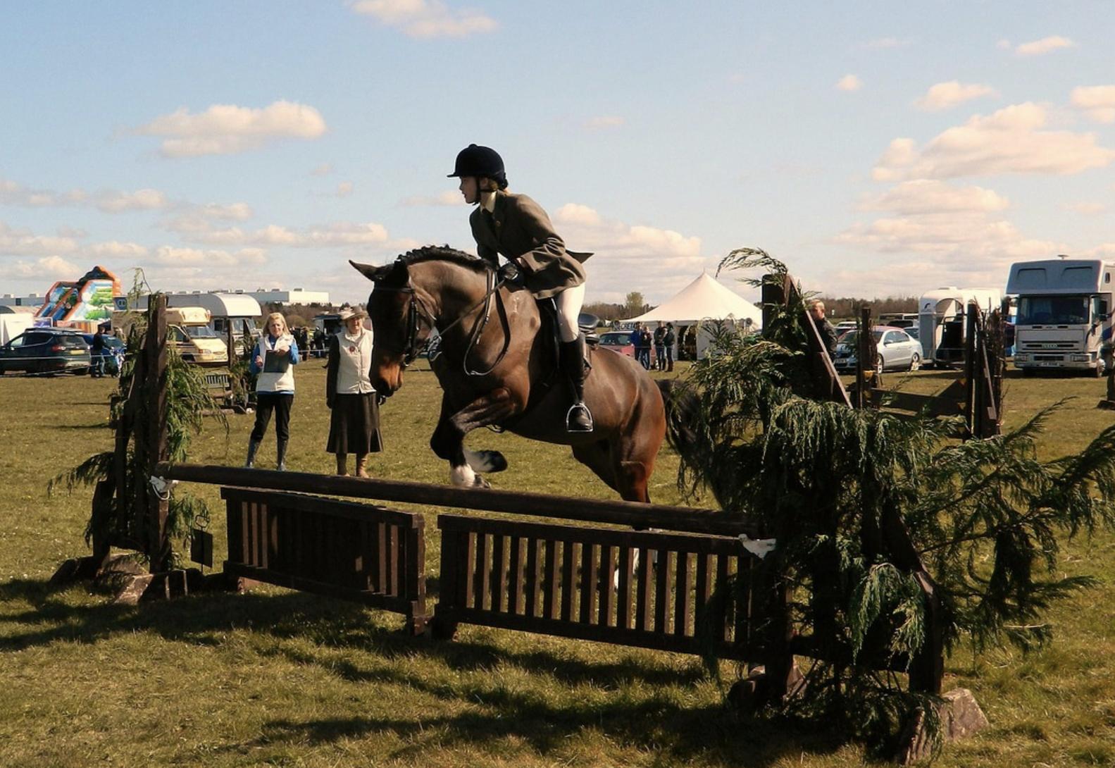 Rider in tan coat jumps a rustic jump