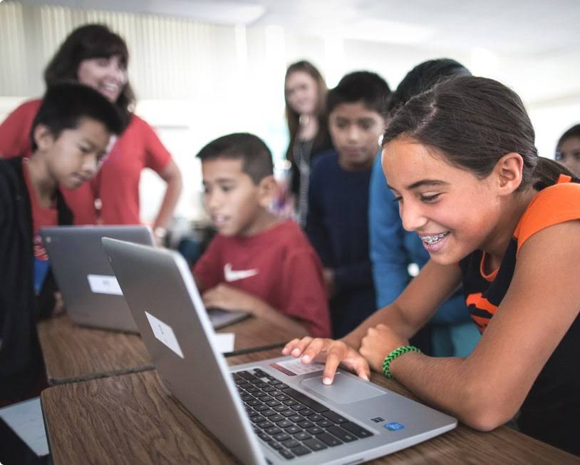 Young girl with braces is smiling while looking at a Chromebook in a classroom full of students.