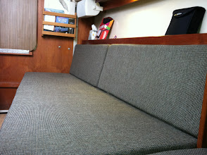 Photo: starboard settee slides out to make double berth, storage behind, 40 gallon water tank under